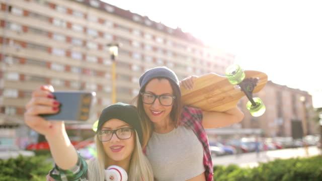 vídeos de stock e filmes b-roll de hipster de skate meninas fazendo selfie - skate liberdade gorro