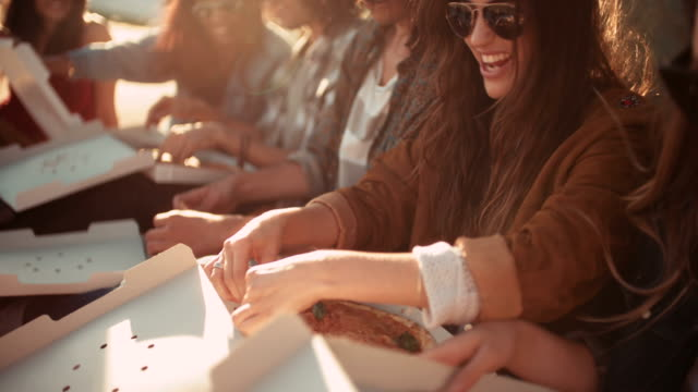 Hipster style friends enjoying pizza at sunset during road trip video