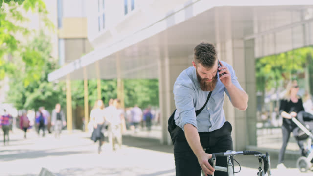 DS Hipster talking on a mobile phone while riding a bicycle in the city video