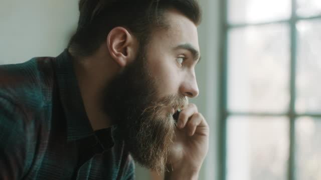 vídeos de stock, filmes e b-roll de hipster falando ao telefone no atelier - cerâmica artesanato