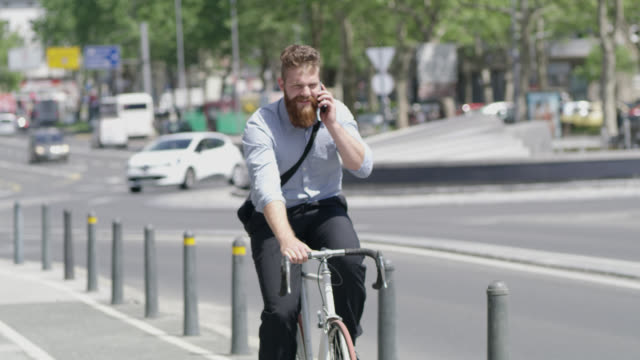 R/F Hipster talking on the phone while riding a bike in the city video