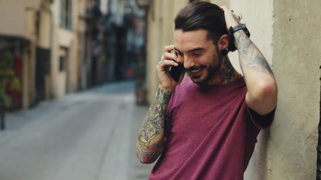 Hipster tattooed man in Barcelona with mobile phone Hipster tattooed man in Barcelona long hair stock videos & royalty-free footage