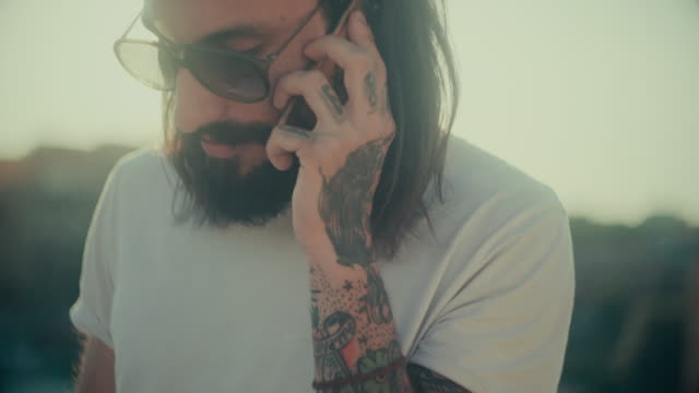 Hipster tattooed rebel guy using mobile phone video
