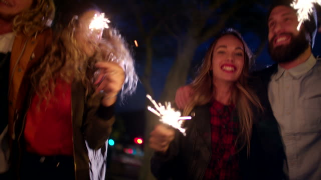 Hipster teen friends celebrating together with sparklers at night video