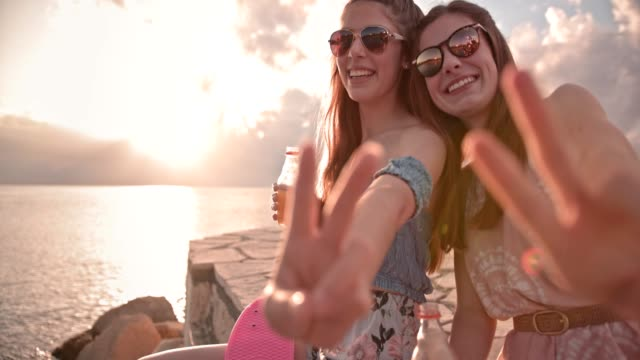 Hipster teenage girls making peace sign and drinking fizzy drinks Teenage best friends relaxing by the sea, making peace sign and drinking soda at sunset soda stock videos & royalty-free footage