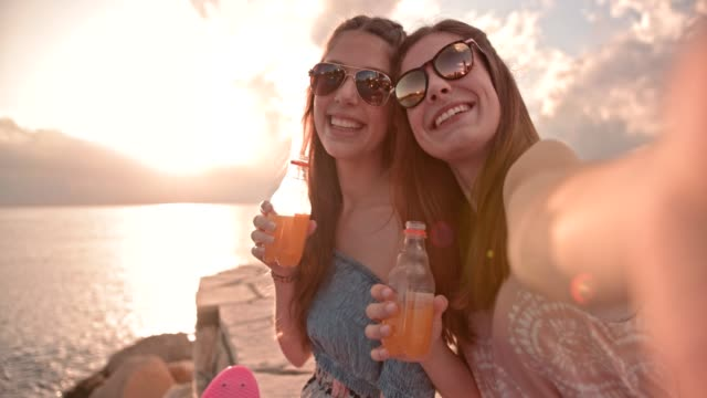 Hipster teenage girls taking selfies and drinking soda at beach Teenage best friends taking selfies on smartphone, relaxing by the sea and drinking fizzy drinks orange juice stock videos & royalty-free footage