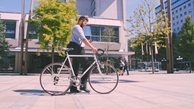 vidéos et rushes de slo mo hipster en utilisant un téléphone portable tandis que dans la ville - vue latérale