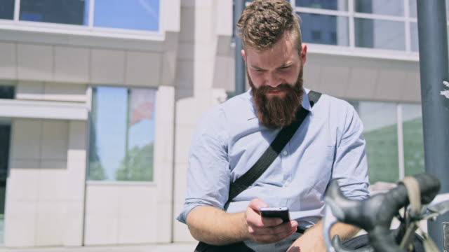 DS Hipster using a smartphone in front of the office building video