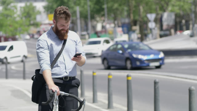 LS Hipster using a smartphone on his bike in the city video