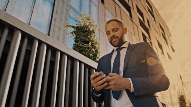 일몰에 사무실 건물을 따라 걷는 동안 스마트 폰을 사용하여 slo mo 힙스터 - 중년 남자 스톡 비디오 및 b-롤 화면