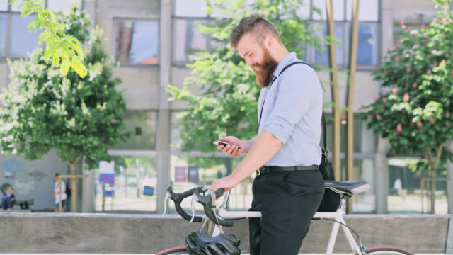 DS Hipster with a bicycle using a smartphone in the city video