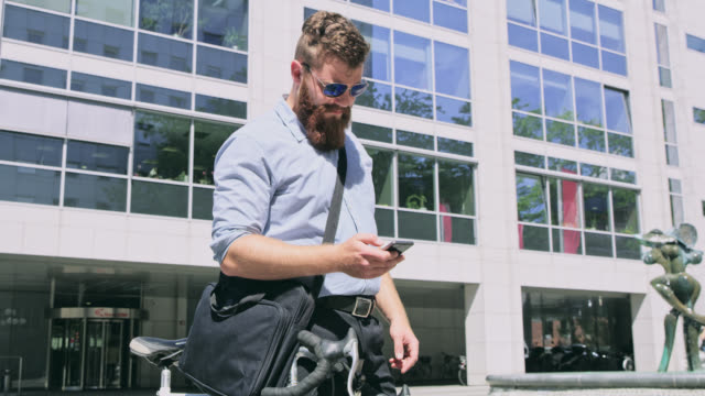 DS Hipster with sunglasses using a smart phone in the city video
