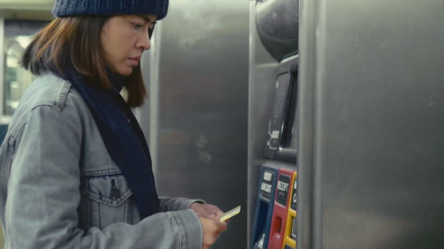 Hipster woman buy the ticket by automatic ticket dispenser Asian tourist buying train tickets from the station, by using a ticket vending machine in New York city. USA new york city subway stock videos & royalty-free footage