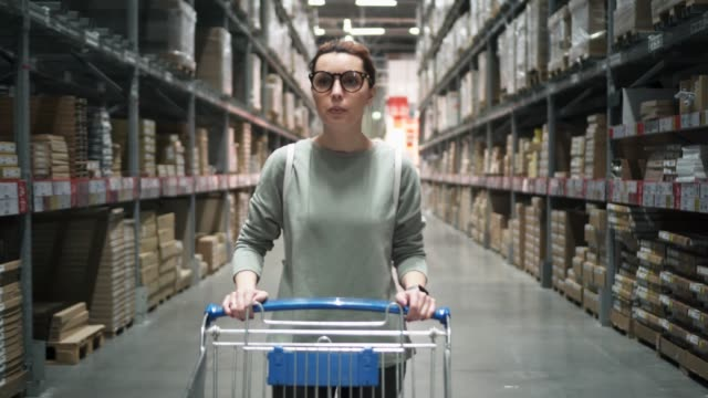 Hipster woman in glasses in store is buying goods. Beautiful woman is driving a shopping trolley in store. Girl do shopping video