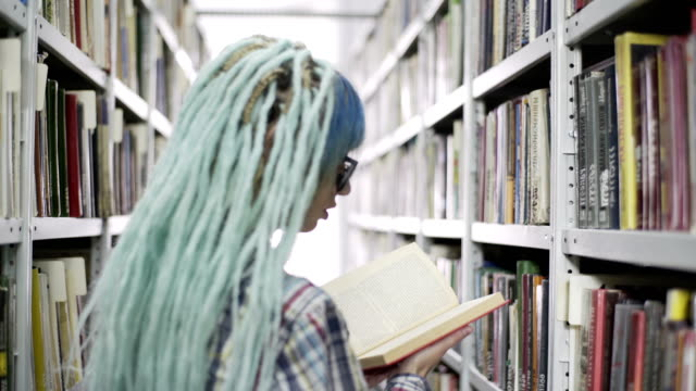 Hipster Woman Reading A Book In Library Portrait of a hipster woman reading book in library blue hair stock videos & royalty-free footage