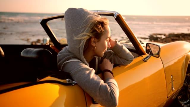Mulher de hipster relaxante em carro conversível e olhando o pôr do sol - vídeo
