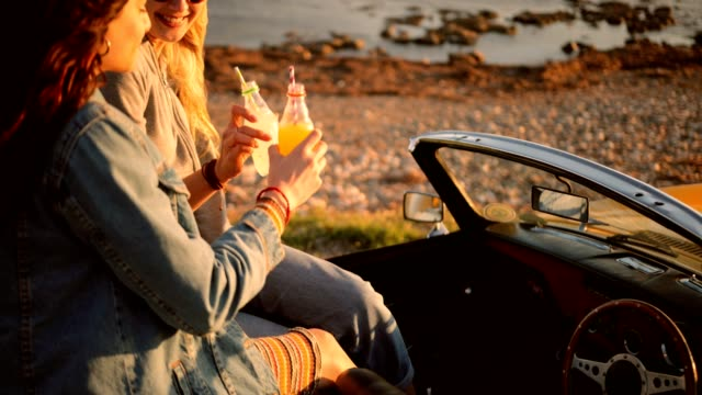 Hipster women in retro convertible car drinking soda at beach Women on road trip with convertible car relaxing at sunset and drinking soda at beach car rental stock videos & royalty-free footage