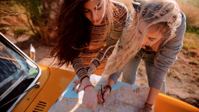 Hipster women on road trip reading map and planning route