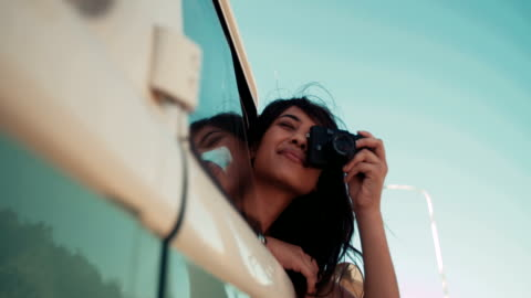 Hipster young adult girl taking a picture from a van Young adult girl dressed in hipster style taking a picture from a vintage car during a road trip boho stock videos & royalty-free footage