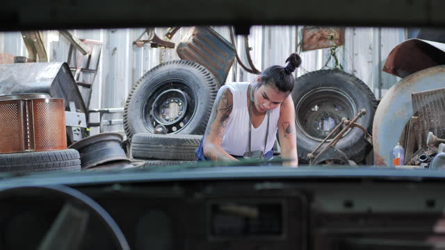 Hipterof asian young women having tattooes on arms she scrubbing the car body in workshop.Women in Blue Collar Jobs.Women in Blue Collar Jobs