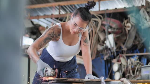 vídeos y material grabado en eventos de stock de hipterof mujeres jóvenes asiáticas con tatuajes en los brazos, ella es soldadora usando sierra circular en el taller. - aleación
