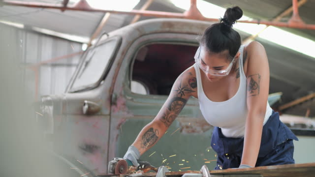 Hipterof asian young women having tattooes on arms, she's welder using circular saw in workshop.