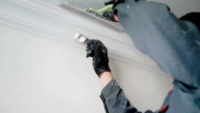 inhyrda builder målar tak sockel - painting wall bildbanksvideor och videomaterial från bakom kulisserna