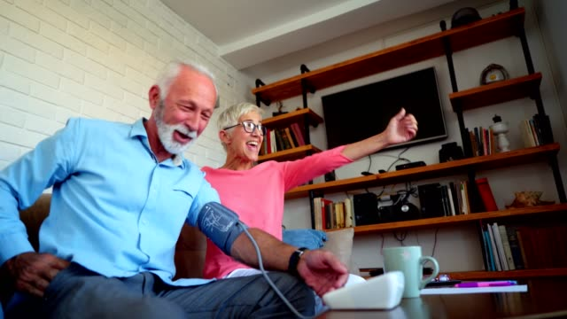 His blood pressure is very good Senior man is talking on cell phone after he found that his blood pressure is good. His wife is looking forward. medicare stock videos & royalty-free footage