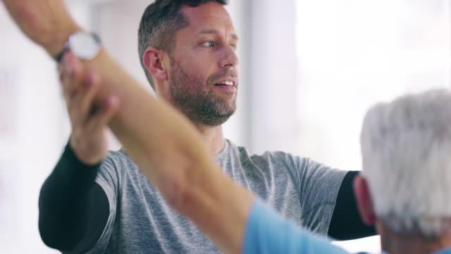 sein ziel ist es, seinen patienten fit zu machen - ausbilder stock-videos und b-roll-filmmaterial