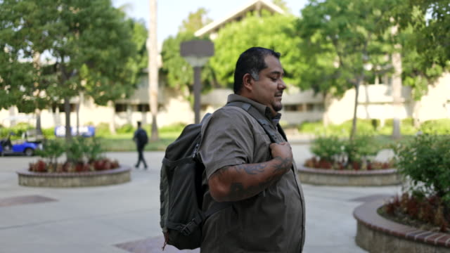 Hispanic American Veteran College Student Walking on Campus A young Hispanic American Veteran college student going to class. He is a double amputee. camouflage clothing stock videos & royalty-free footage