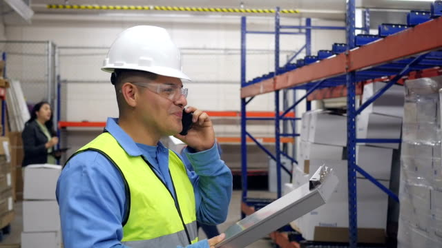 Hispanic blue collar worker in warehouse taking shipment order over phone video