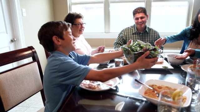 Hispanic boy passing food around dinner table with multi-generational family