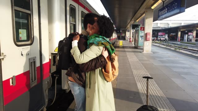 Hispanic brazilian couple in Italy - traveling county by train Hispanic brazilian couple in Italy - traveling county by train railroad station platform stock videos & royalty-free footage