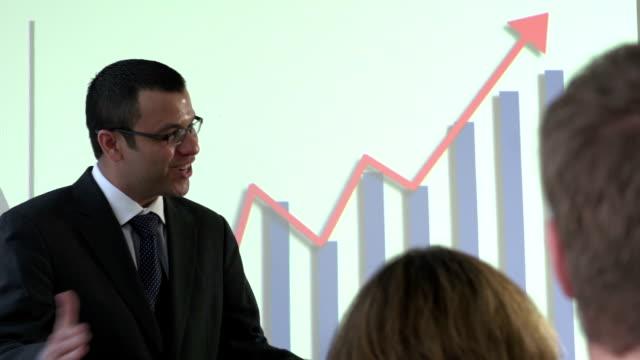 Hispanic Business man presenting the company's profits video
