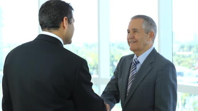 Hispanic businessman greetiing caucasian businessman video