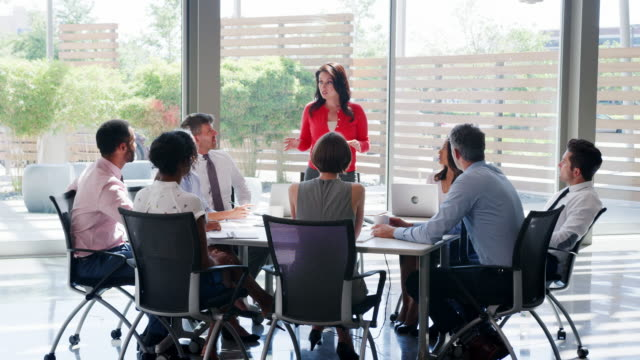 A Hispanic businesswoman holds a meeting in a modern office