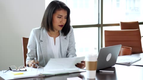 Hispanic businesswoman is frustrated while working in her office Young Hispanic businesswoman uses a laptop while in her office or conference room. She sits back and sighs deeply while looking at the laptop. She takes off her reading glasses and picks up a chart or graph. While looking at the chart, she also looks at the laptop. examining stock videos & royalty-free footage