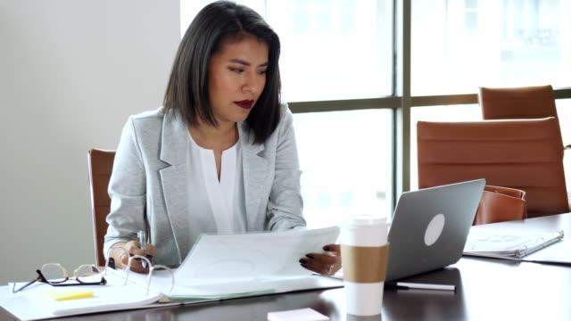 hispanic businesswoman is frustrated while working in her office - sprawdzać filmów i materiałów b-roll