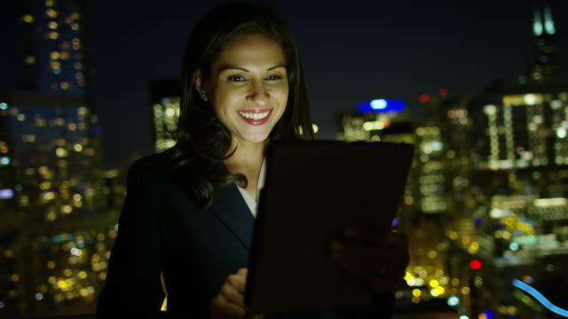 Hispanic businesswoman using touchscreen on rooftop at night video