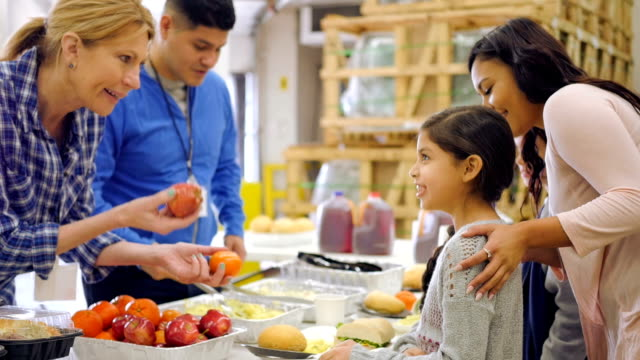 Hispanic child choosing healthy food in line at soup kitchen video