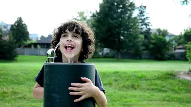 Hispanic Child Drinking from Water Fountain video
