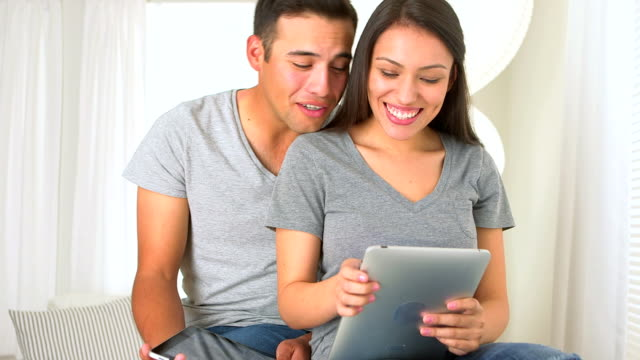 Hispanic couple using a tablet medium shot, selective focus, front view, looking down,  surfing the net stock videos & royalty-free footage