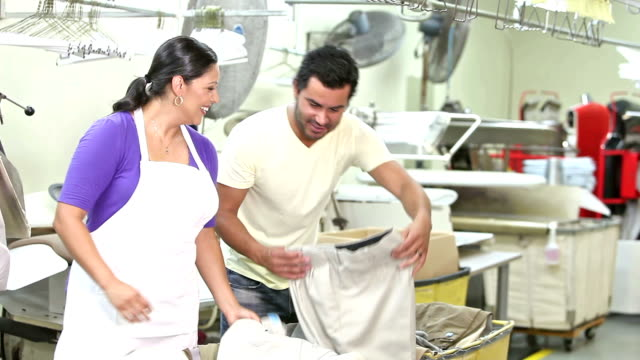 Hispanic couple working in dry cleaner store video