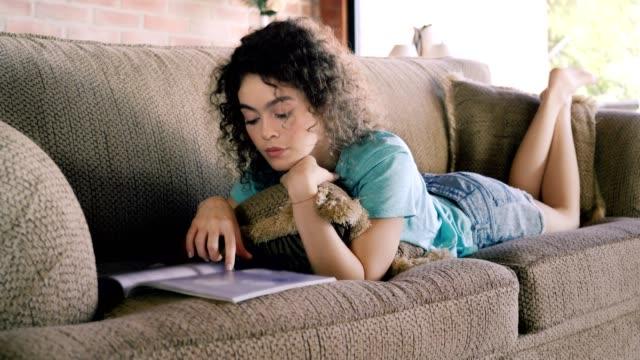 stockvideo's en b-roll-footage met hispanic krullend haar jonge vrouw het lezen van een tijdschrift terwijl ontspannen op een bank - woman home magazine