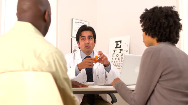 Hispanic doctor talking to African American couple about prescription video