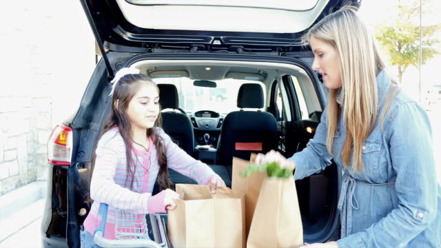 Hispanic elementary age daughter is helping mother load brown paper grocery bags in minivan or SUV outside of grocery store video