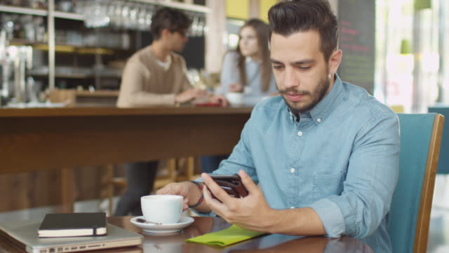 hispanic ethnicity young man using mobile phone at cozy coffee shop. - caffetteria video stock e b–roll