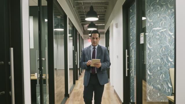 hispanic executive walking in hallway using digital tablet - widok od przodu filmów i materiałów b-roll