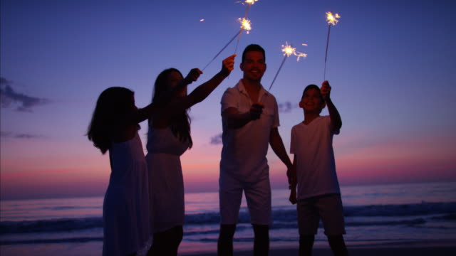 Hispanic family at sunset with sparklers on beach video