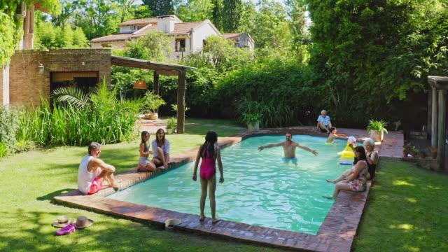 vídeos y material grabado en eventos de stock de familia hispana divirtiéndose en la piscina - backyard pool